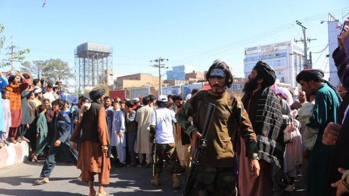 Orang-orang berkumpul di alun-alun kota Herat di barat Afghansitan, di mana Taliban menggantung mayat terduga penculik menggunakan crane pada Sabtu, 25 September 2021. Taliban mengumumkan jasad itu digantung sebagai peringatan jika ada yang hendak berbuat jahat.(AP PHOTO/-)