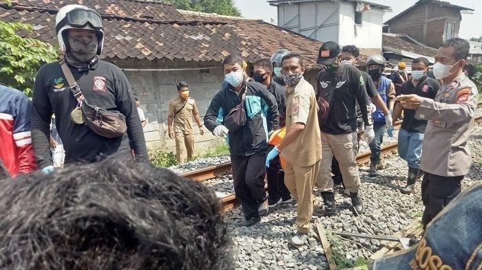 Petugas mengevakuasi jenazah Ruslan (85) di perlintasan kereta api relasi Solo-Semarang, Kecamatan Banjarsari, Kota Solo, Senin (31/5/2021).