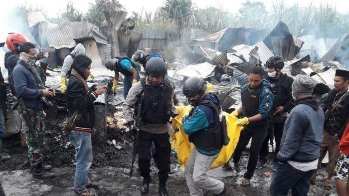 Petugas mengevakuasi jasad Hendrik Simatupang yang menjadi korban tewas dalam aksi perusakan massa disertai pembakaran di Kampung Ikebo, Distrik Kamuu, Kabupaten Dogiyai, Papua, Kamis (16/7/2021) malam.