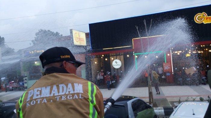 Petugas pemadam kebakaran menyemprotkan disinfektan di sepanjang Jalan Pancasila Kota Tegal, Minggu (27/12/2020).