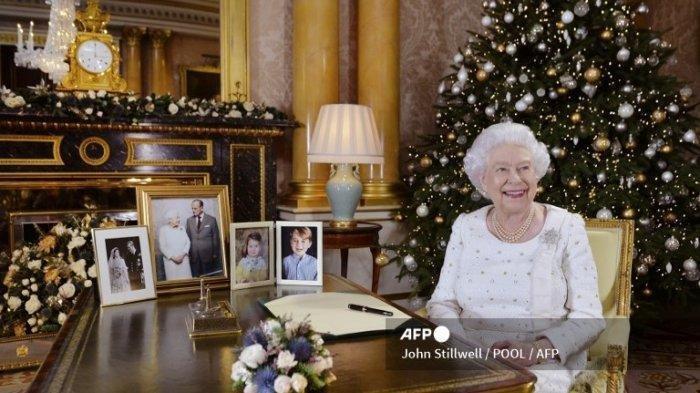 Ratu Elizabeth II dari Inggris berpose di sebuah meja di Kamar 1844 di Istana Buckingham, London, pada 13 Desember 2017 setelah merekam siaran Hari Natalnya ke Persemakmuran.