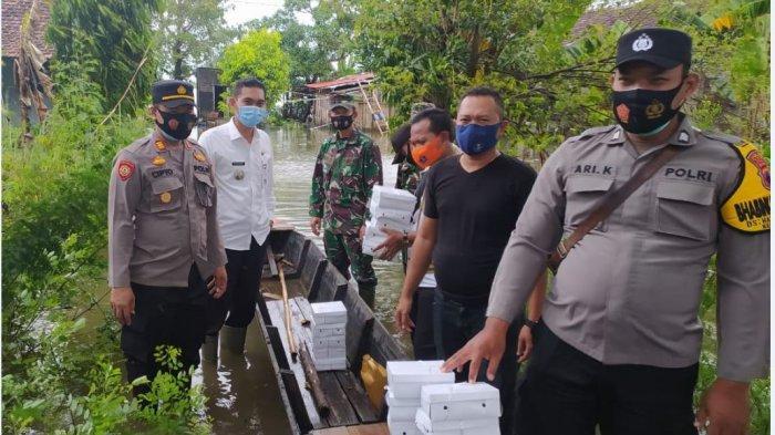 Relawan bencana membagikan nasi bungkus kepada warga terdampak banjir di Kecamatan Mejobo.