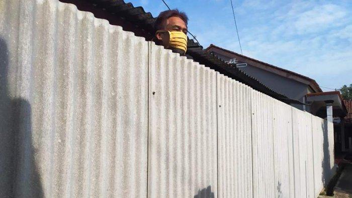 Sabar Suharno (45), Warga RT 2 RW 10, Desa Ajibarang Wetan, Kecamatan Ajibarang, Kabupaten Banyumas memasang seng keliling dirumahnya karena takut tertular virus Corona, pada Jumat (8/1/2021).