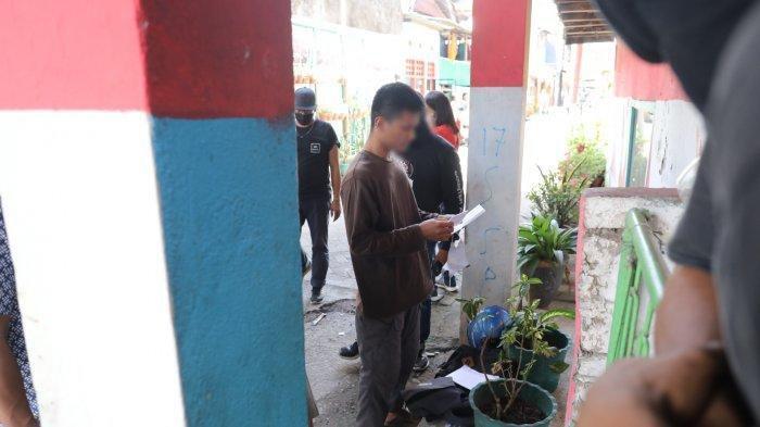 Salah seorang warga diperiksa oleh polisi saat memasuki Jl Tinumbu 1, Lrg 132, Makassar, Senin (29/3/2021).