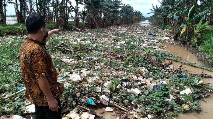 Perangkat desa menunjukkan sampah yang menumpuk di Sungai Piji ?2, Kesambi, Mejobo, Kabupaten Kudus, Rabu (24/2/2021).