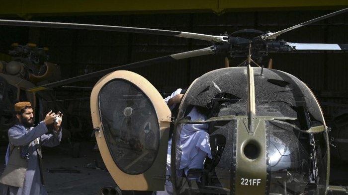 Seorang pejuang Taliban (kiri) mengambil gambar helikopter MD 530 Angkatan Udara Afghanistan yang rusak dengan ponselnya di dekat hanggar di bandara di Kabul pada 31 Agustus 2021, setelah AS menarik semua pasukannya keluar dari negara itu.