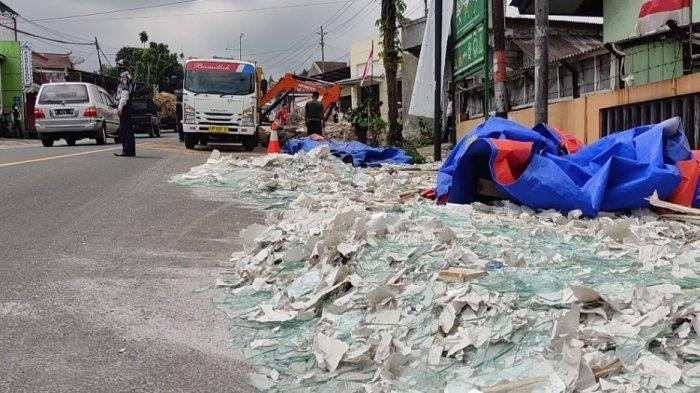 Serpihan kaca muatan truk berserakan di pinggir jalan di Desa Candimulyo Kertek, Wonosobo setelah terlibat kecelakaan lalu linta.