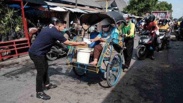 Salah satu tim Satgas BUMN dari CSR PTSG membagikan 1 set masker kepada pedagang di Pasar Sarang, Kabupaten Rembang.