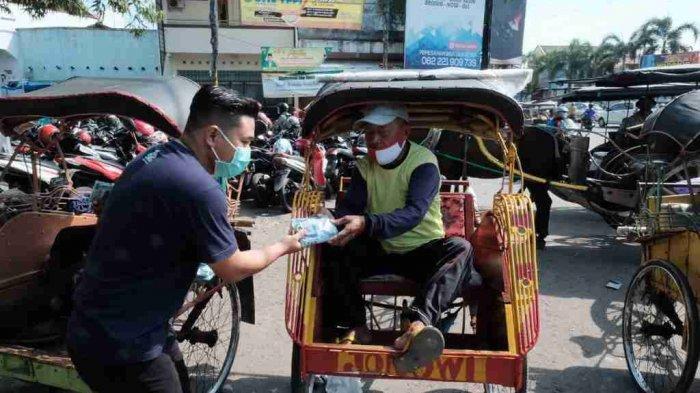 Satu set Masker dan handsanitizer dibagikan kepada penarik becak di Pasar Kota Rembang.