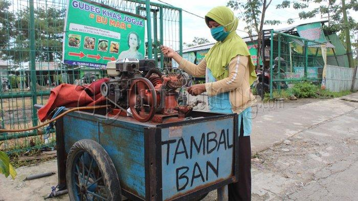 Sri Sutini (41) Ibu satu anak membuka jasa tambal ban akibat suaminya alami kebutaan sehingga tak lagi bisa bekerja di Jalan Tambak Dalam Raya, Gayamsari, Kota Semarang atau di sisi timur SPBU Masjid Agung Semarang, Senin (9/3/2021).
