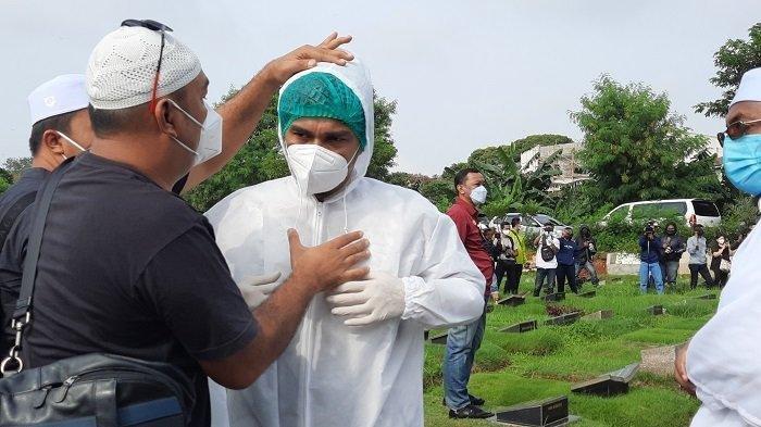 Teddy Syach saat memakai APD saat ikut memakamkan istrinya, Rina Gunawan, di TPU Tanah Kusir Jakarta Selatan, Selasa (3/3/2021).