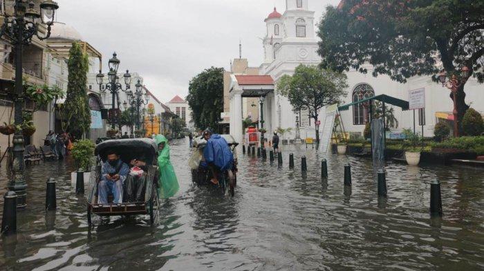 Warga asyik bersantai dan berswa foto di Kawasan Kota Lama Semarang yang terendam banjir, Sabtu (6/2/2021)
