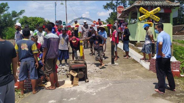 Sejumlah warga Dukuh Siboto, Desa Kalimacan, Kecamatan Kalijambe ketika bersujud syukur dibukanya portal besi palang kereta api, Kamis (18/2/2021).