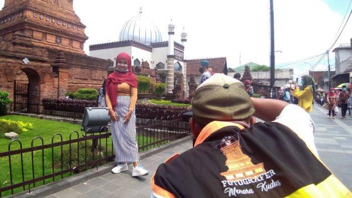 Fotografer ?Menara Kudus tengah memotret wisatawan religi yang datang di Masjid Menara Sunan Kudus.