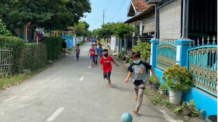 Suasana di Desa Balamoa RT 03 RW 06, Kecamatan Pangkah, Kabupaten Tegal yang melakukan lockdown PPKM Mikro karena ditemukan 14 warganya terpapar Covid-19, Jumat (18/6/2021). Terlihat petugas sedang berjaga di pintu masuk area Desa dan ada anak-anak yang sedang bermain bola.
