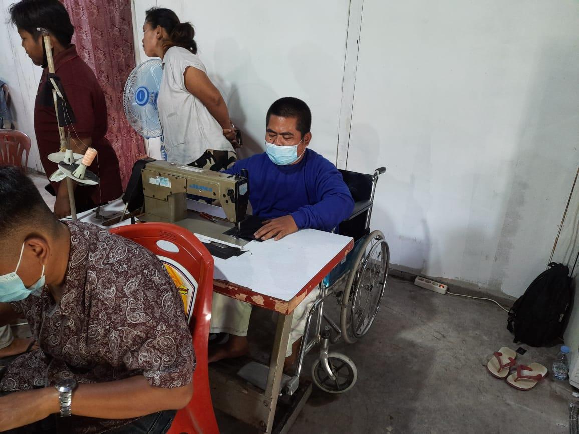 Di atas kursi roda, salah satu anggota Difablepreneur serius menjahit.