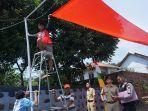 abdul-hadi-saat-memasangkan-bendera-dengan-penyangga-bambu.jpg