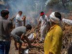 anggota-keluarga-korban-covid-19-menyiapkan-tumpukan-kayu-di-krematorium-di-new-delhi-india.jpg
