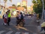 anggota-polres-tegal-kota-sedang-menyeberangkan-siswa-di-jalan-kartini-kota-tegal.jpg