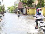 pengendara-sepeda-motor-melintas-di-jalan-gebanganom-kelurahan-gebangsari-yang-terendam-banjir.jpg