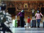 penumpang-berjalan-dengan-barang-bawaan-mereka-saat-tiba-di-bandara.jpg