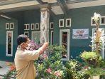 perangkat-desa-menunjukkan-rumah-yang-ditempeli-banner-penerima-bantuan-pkh-dan-bpnt.jpg