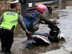petugas-kepolisian-membantu-mendorong-sepeda-motor-di-jalan-kaligawe-raya.jpg