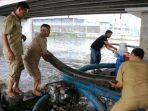 sejumlah-pekerja-dari-dinas-pekerjaan-umum-kota-semarang-menangani-banjir-kaligawe.jpg