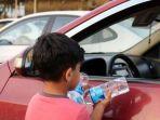 seorang-anak-menjual-air-mineral-ke-pengendara-mobil-di-jalan-kota-mosul-irak-utara_20180708_202102.jpg