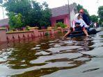 seorang-bocah-menaiki-ban-di-atas-genangan-banjir-di-desa-jati-wetan-kecamatan-jati-kudus.jpg