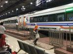 seorang-calon-penumpang-menaiki-kereta-api-ka-di-stasiun-semarang-poncol.jpg
