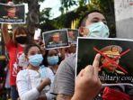 seorang-migran-myanmar-memegang-poster-dengan-gambar-kepala-jenderal-senior-min-aung-hlaing.jpg