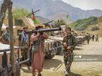 seorang-milisi-berdiri-bersama-anggota-pasukan-pemerintah-afghanistan.jpg