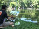 seorang-pelukis-sedang-membuat-lukisan-dengan-objek-wisata-air-senjoyo.jpg