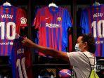 seorang-pembeli-melihat-jerseys-bertuliskan-nama-penyerang-barcelona-argentina-lionel-messi.jpg
