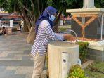 seorang-pengunjung-terlihat-mencuci-tangan-di-keran-yang-tersedia-di-alun-alun-kabupaten-pati.jpg