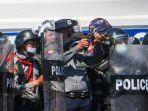 seorang-polisi-tengah-mengacungkan-senapannya-dalam-bentrokan.jpg