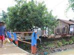 seorang-warga-melintas-di-depan-rumah-rusak-parah-akibat-luapan-sungai-winong-seting.jpg