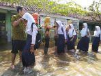 siswa-siswi-sdn-sayung-4-demak-yang-tergenang-banjir-bersalaman-dengan-guru-guru.jpg