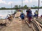 warga-bergotong-royong-membuat-jalan-sak-sak-yang-terbuat-dari-bambu.jpg