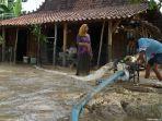 warga-menyedot-air-sisa-banjir-untuk-membersihkan-rumahnya.jpg