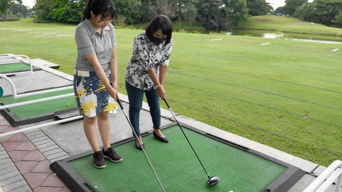 DIGEMARI MILLENIAL - Maura saat berlatih golf di driving range Bukit Darmo Golf, Rabu (24/2). Saat pandemi, banyak kaum muda (millenial) berlatih golf untuk berolahraga.