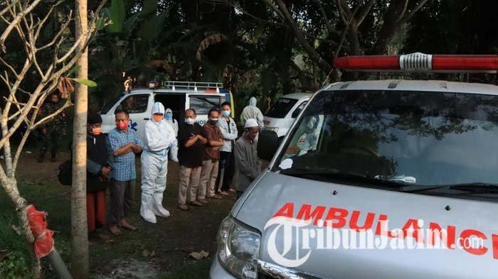 Petugas bersama keluarga jenazah pasien Covid-19 menunaikan salat jenazah di samping ambulance sebelum akhirnya dikebumikan di pemakaman umum Desa Sekarpuro, Kecamatan Pakis, Kabupaten Malang, Jumat (2/7/2021).