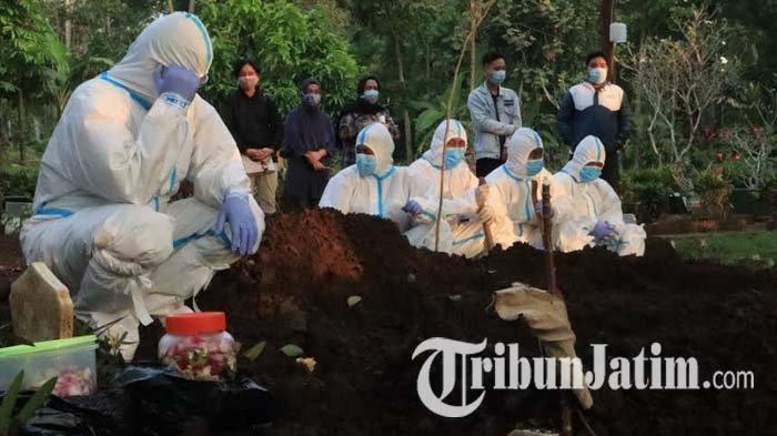 Petugas pemakaman jenazah Covid-19 mengumandangkan azan sesaat setelah jenazah dikebumikan di pemakaman umum Desa Sekarpuro, Kecamatan Pakis, Kabupaten Malang, Jumat (2/7/2021).