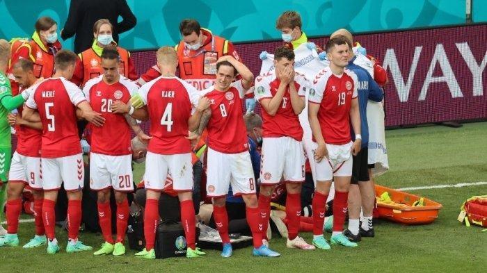 Para pemain Denmark berkumpul saat paramedis merawat gelandang Christian Eriksen (tidak terlihat) selama pertandingan sepak bola Grup B UEFA EURO 2020 antara Denmark dan Finlandia di Stadion Parken di Kopenhagen pada 12 Juni 2021.