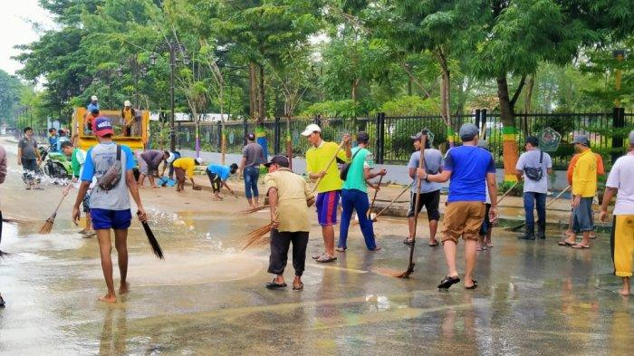 Puluhan Personel Kebersihan DLH Pamekasan Bersihkan Sisa Lumpur Banjir di Jalan Raya