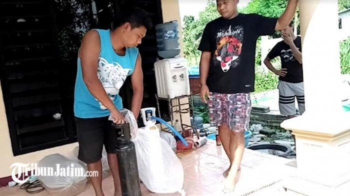 Ketua Kelompok Sol Koi di Kecamatan Sumbergempol, Alipin mengisi kantong plastik dari tabung oksigen yang diduga palsu.
