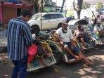 anggota-lsm-perspektif-indonesia-bagikan-paket-bantuan-sosial-kepada-tukang-becak-di-nganjuk.jpg