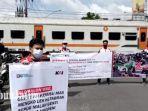 anggota-railfans-kota-marmer-tulungagung-membentangkan-tulisan-kampanye-kereta-api.jpg