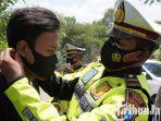 berita-gresik-anggota-satlantas-polres-gresik-saat-memakaikan-masker.jpg